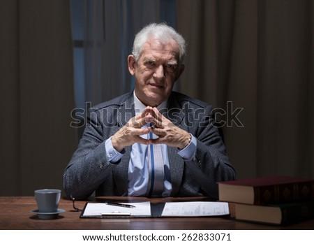Senior businessman sitting at the office desk - stock photo