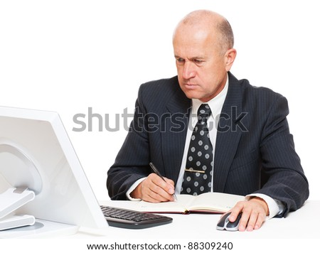 senior businessman sitting in workplace and writing in datebook