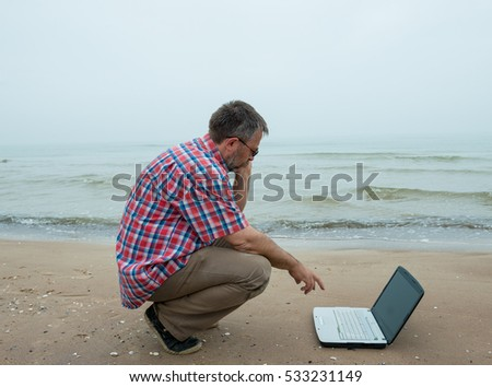Senior businessman sitting with notebook at the beach