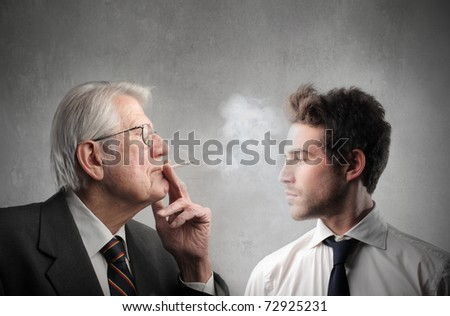 Senior businessman smoking in front of a younger one - stock photo