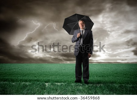 senior businessman standing with umbrella in the countryside under the rain