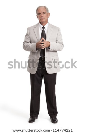Senior Businessman stands with hands together - stock photo