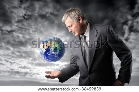senior businessman taking care of planet earth against a stormy sky - stock photo