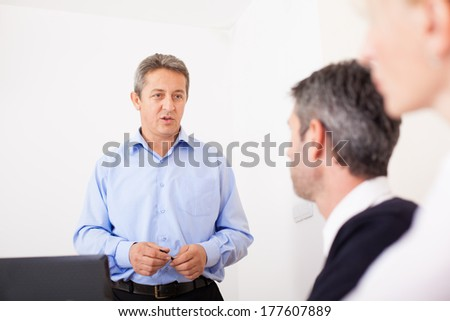 Senior businessman talking at business seminar. - stock photo