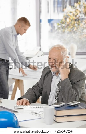 Senior businessman talking on landline phone sitting at office desk, young colleague working in background.?