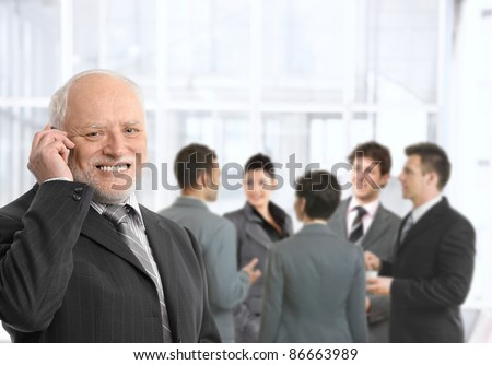 Senior businessman talking on mobile phone in office lobby, smiling, businesspeople chatting in background.? - stock photo