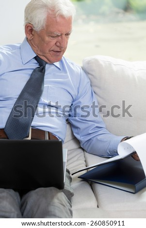 Senior businessman using a laptop and looking at notes - stock photo