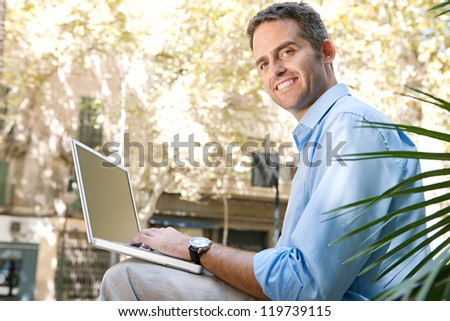 Senior businessman using a laptop computer while sitting on a bench in the city, turning to camera. - stock photo