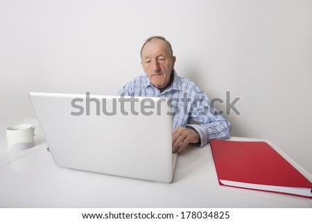 Senior businessman using laptop at office desk - stock photo