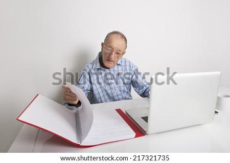 Senior businessman using laptop while reading file at office desk - stock photo