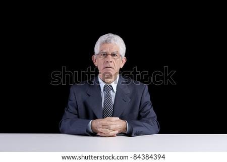 Senior businessman waiting at his desk  (isolated on black) - stock photo