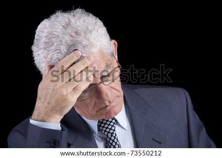 Senior businessman with an headache (isolated on black) - stock photo