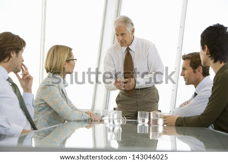 Senior businessman with colleagues having a discussion in conference room - stock photo