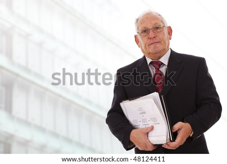 senior businessman with documents next to his office - stock photo
