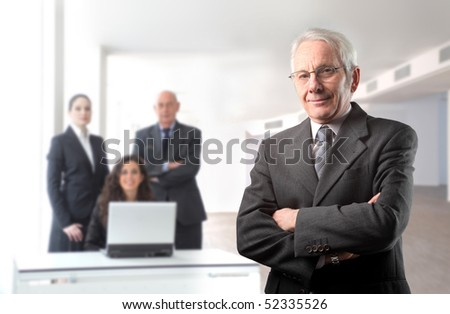 Senior businessman with group of business people on the background - stock photo