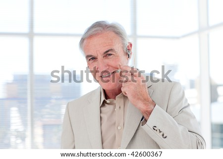 Senior businessman with headset on smiling at the camera - stock photo