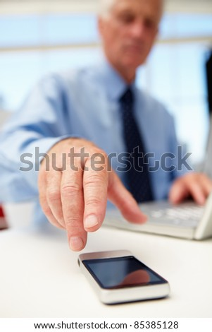 Senior businessman with laptop and phone - stock photo