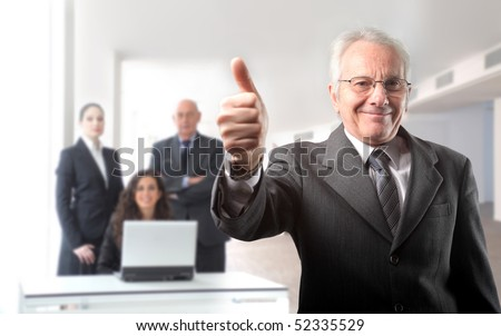 Senior businessman with thumbs up and group of business on the background - stock photo