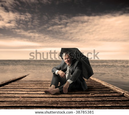 senior businessman with umbrella on a wharf - stock photo