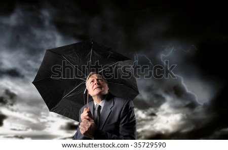 senior businessman with umbrella under a stormy sky - stock photo