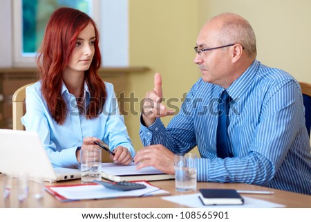 Senior businessman with young redhead female colleague discuss something - stock photo