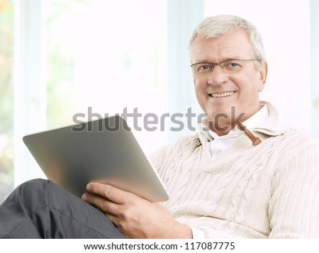 Senior businessman working and using a tablet - stock photo