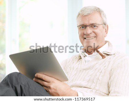 Senior businessman working and using a tablet