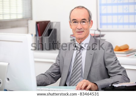 Senior businessman working at a computer - stock photo