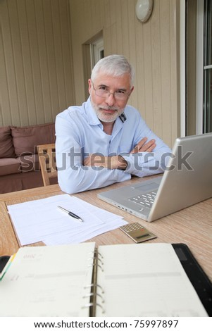 Senior businessman working at home - stock photo