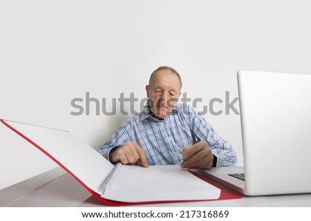 Senior businessman working at office desk - stock photo