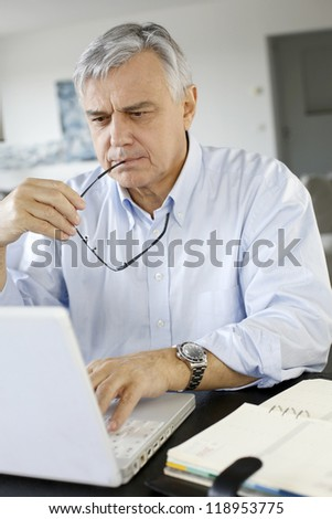 Senior businessman working from home on laptop - stock photo