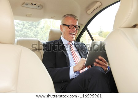 Senior businessman working in back of car and using a tablet
