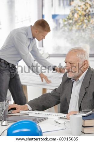 Senior businessman working on computer sitting at table, young architect standing at drawing board in background.? - stock photo