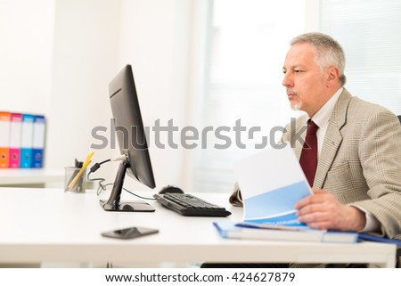 Senior businessman working on his computer while reading a document - stock photo