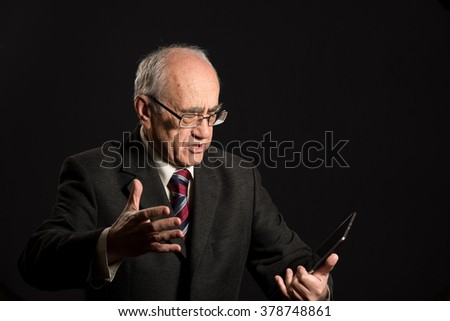 senior businessman works with tablet pc, in trouble, angry