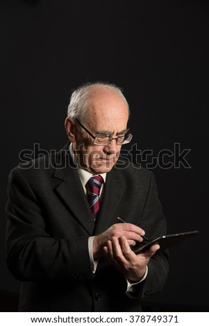 senior businessman works with tablet pc, looking serious