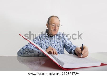 Senior businessman writing in file at desk - stock photo