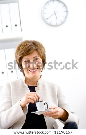 Senior businesswoman sitting and smiling at office and drinking coffee. - stock photo