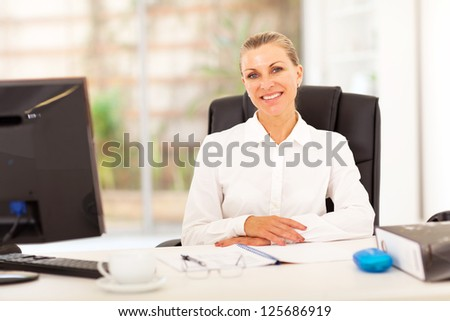 senior businesswoman sitting in front of desk in office - stock photo