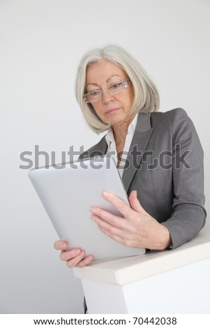 Senior businesswoman using electronic tablet in hall