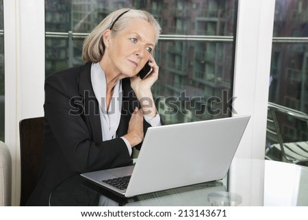 Senior businesswoman with laptop using cell phone while sitting at table - stock photo