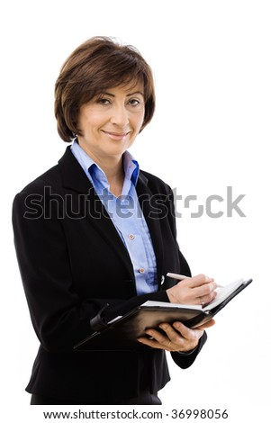 Senior businesswoman writing notes, smiling and looking at camera. Isolated on white background.