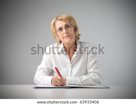 Senior businesswoman writing on a register - stock photo