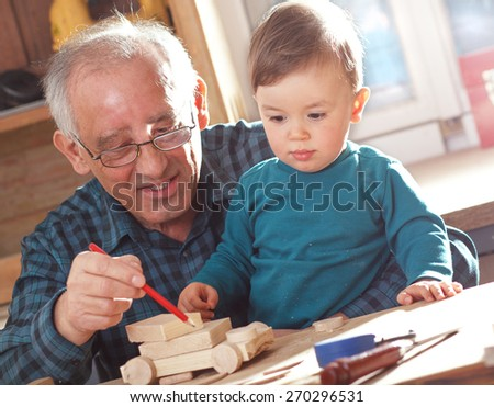 Senior carpenter and his grandson working in the workshop - stock photo