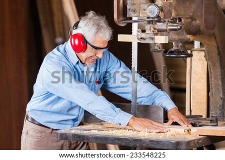 Senior carpenter cutting wood with bandsaw in workshop - stock photo