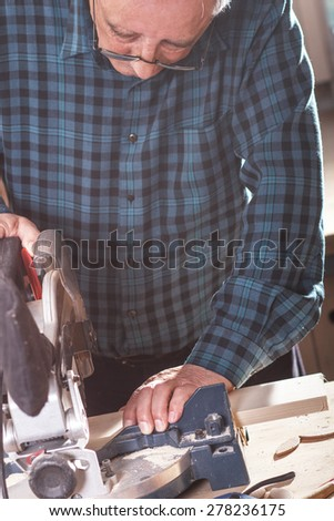 Senior carpenter cutting wooden plank with circular saw