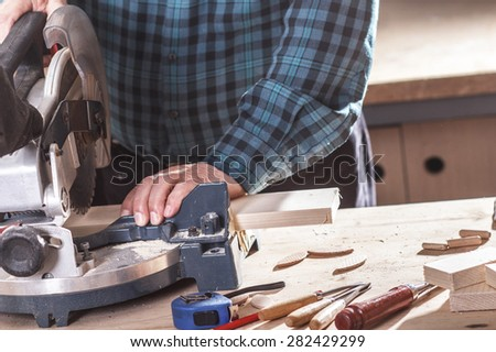 Senior carpenter cutting wooden plank with circular saw - stock photo