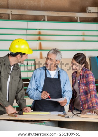 Senior carpenter discussing over document with team in workshop - stock photo