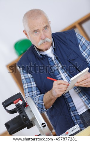 senior carpenter holding clipboard and making notes