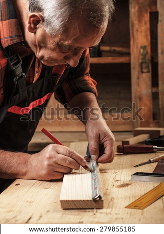 Senior carpenter marking a measurement on a wooden plank - stock photo